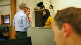 Estudiantes que charlan con el conferenciante en sala de ordenadores almacen de video