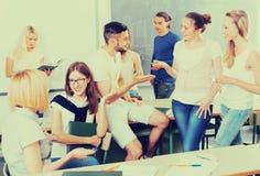 Estudiantes que charlan mientras que se sienta en el cuarto Fotografía de archivo libre de regalías
