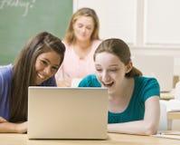 Estudiantes que comparten la computadora portátil en sala de clase imágenes de archivo libres de regalías