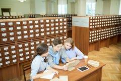 Estudiantes que consiguen nuevo conocimiento en biblioteca fotos de archivo