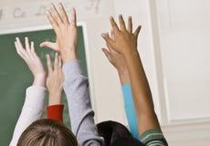 Estudiantes que contestan a la pregunta del profesor Imagen de archivo