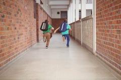 Estudiantes que corren abajo del pasillo de la escuela Foto de archivo libre de regalías