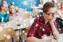 Estudiantes que cotillean detrás de la parte posterior del compañero de clase en la escuela Imágenes de archivo libres de regalías