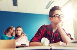 Estudiantes que cotillean detrás de la parte posterior del compañero de clase en la escuela Fotografía de archivo libre de regalías