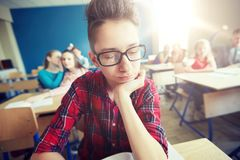 Estudiantes que cotillean detrás de la parte posterior del compañero de clase en la escuela Fotografía de archivo