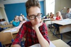 Estudiantes que cotillean detrás de la parte posterior del compañero de clase en la escuela Fotos de archivo