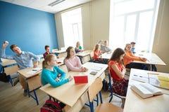 Estudiantes que cotillean detrás de la parte posterior del compañero de clase en la escuela Foto de archivo libre de regalías