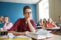 Estudiantes que cotillean detrás de la parte posterior del compañero de clase en la escuela Imagen de archivo libre de regalías