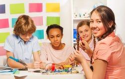 Estudiantes que crean el modelo de cadena eléctrico en el escritorio Imágenes de archivo libres de regalías