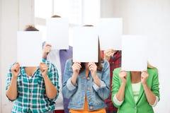 Estudiantes que cubren caras con los papeles en blanco Foto de archivo libre de regalías