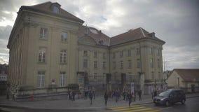 Estudiantes que cuelgan hacia fuera cerca del edificio viejo de la universidad, tráfico de coche en la calle almacen de metraje de vídeo