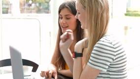 Estudiantes que cuelgan hacia fuera en café del campus usando el ordenador portátil metrajes