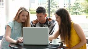 Estudiantes que cuelgan hacia fuera en café del campus usando el ordenador portátil almacen de video