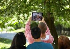 Estudiantes que cuelgan hacia fuera y que toman el selfie en un parque Fotografía de archivo libre de regalías