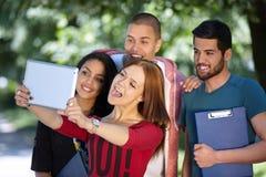 Estudiantes que cuelgan hacia fuera y que toman el selfie en un parque Fotos de archivo libres de regalías