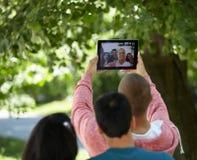 Estudiantes que cuelgan hacia fuera y que toman el selfie en un parque Fotografía de archivo