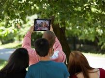 Estudiantes que cuelgan hacia fuera y que toman el selfie en un parque Foto de archivo libre de regalías