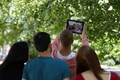 Estudiantes que cuelgan hacia fuera y que toman el selfie en un parque Imagen de archivo libre de regalías