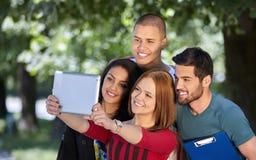 Estudiantes que cuelgan hacia fuera y que toman el selfie en un parque Foto de archivo