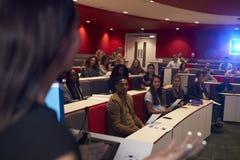 Estudiantes que dan una conferencia de la mujer en el teatro de conferencia, midground del foco Fotografía de archivo libre de regalías