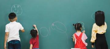 Estudiantes que dibujan en tablero verde imagenes de archivo