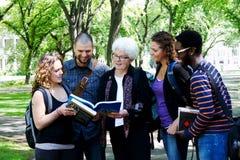 Estudiantes que disfrutan de una risa con el profesor Foto de archivo libre de regalías