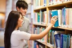 Estudiantes que eligen un libro en un estante Imagenes de archivo