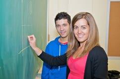 Estudiantes que escriben en la pizarra Imagenes de archivo