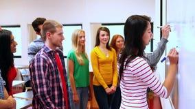 Estudiantes que escriben en whiteboard en sala de clase almacen de metraje de vídeo