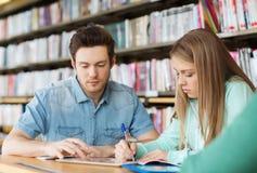 Estudiantes que escriben a los cuadernos en biblioteca Imagenes de archivo