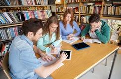 Estudiantes que escriben a los cuadernos en biblioteca escolar Imágenes de archivo libres de regalías