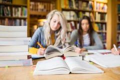 Estudiantes que escriben notas con la pila de libros en el escritorio de la biblioteca Imagen de archivo