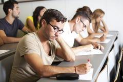 Estudiantes que escriben un examen en sitio de clase