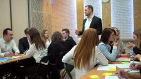 Estudiantes que escuchan y que miran el altavoz en una conferencia Auditorio por completo de estudiantes universitarios atentos J almacen de metraje de vídeo