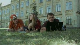 Estudiantes que estudian afuera en campus en un día soleado metrajes