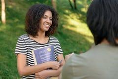 Estudiantes que estudian al aire libre mientras que habla Mirada a un lado Foto de archivo