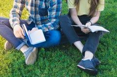 Estudiantes que estudian al aire libre sentarse en la hierba Fotografía de archivo libre de regalías