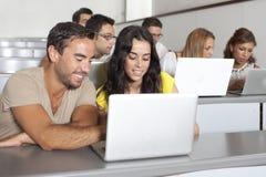 Estudiantes que estudian con el ordenador portátil en sitio de clase Imagen de archivo libre de regalías
