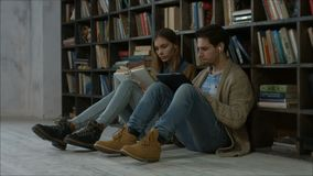 Estudiantes que estudian después de conferencias en la biblioteca metrajes