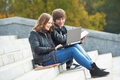 Estudiantes que estudian en línea con el ordenador portátil al aire libre Imagenes de archivo