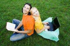 Estudiantes que estudian en parque Imagen de archivo libre de regalías