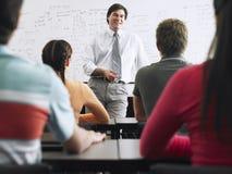 Estudiantes que estudian en sala de clase con el profesor Foto de archivo
