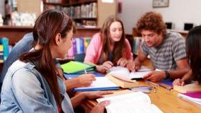 Estudiantes que estudian junto en la biblioteca con la muchacha que sonríe en la cámara metrajes