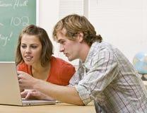 Estudiantes que estudian junto en sala de clase Foto de archivo libre de regalías