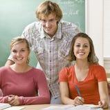 Estudiantes que estudian junto en sala de clase Imágenes de archivo libres de regalías