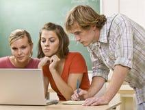 Estudiantes que estudian junto en sala de clase Imagenes de archivo