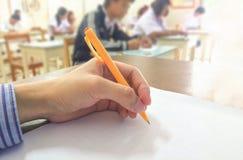 Estudiantes que estudian y que prueban el examen final en sala de clase imagenes de archivo