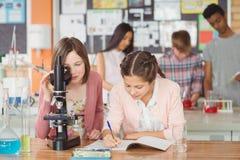 Estudiantes que experimentan en el microscopio en laboratorio en la escuela en laboratorio Fotografía de archivo libre de regalías