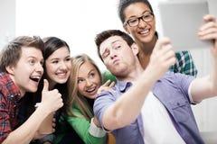 Estudiantes que hacen la imagen con PC de la tableta en la escuela Foto de archivo