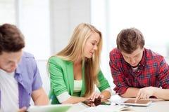 Estudiantes que hojean en PC de la tableta en la escuela Imagenes de archivo